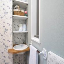 トイレのコーナーに造作の棚と洗面を設置。 クロスと洗面ボウル・タオルハンガーまで統一したこだわりの空間