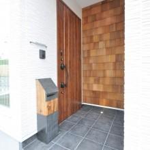 モザイクウッドの外壁、玄関ドア、ポスト、タイル。それぞれの質感が彩る玄関ポーチ。
