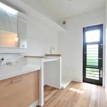 庭につながる勝手口と作業台を設けたサニタリーは、洗濯からアイロン掛けまでを完結できる家事動線が魅力。雨の日も室内干しが可能なスペースがうれしい。