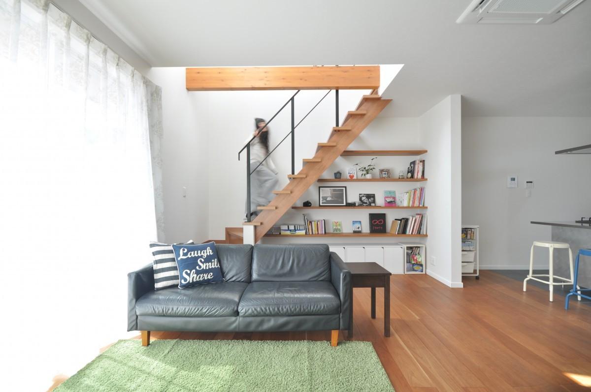 木とアイアンを組み合わせた素材感のあるストリップ階段はご主人、階段下の造作棚は奥さまのこだわり。またウッドデッキへとつながる掃き出し窓からの採光で明るいリビングはいつも家族が集まる場所に。