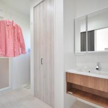 Panasonic × Journal standardの洗面化粧台を採用。浴室前の収納式のワイヤーは部屋干しスペースを可能にしてくれる。