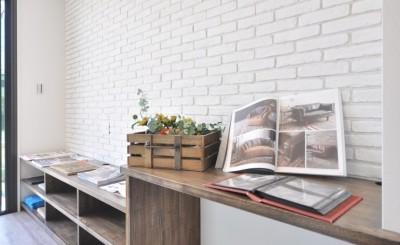 壁には白レンガを貼り、TVボード(奥側)からPC用デスク(手前側)は、タモ材で造作したこだわりのスペース。
