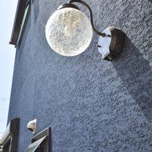 玄関上部にはアンティーク調の照明をチョイス。ネイビーの外壁とも相性◎