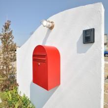 白の塗り壁仕上げの門柱にアンティークな照明と真っ赤なポストは、青空の中での存在感も◎