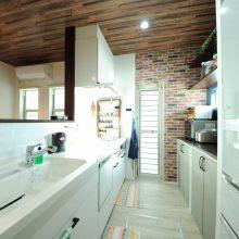 バックセットは造作棚とアンティーク調クロスでLDKの統一感を演出。ひと際映えるホワイトキッチンは奥さまのこだわり。