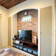 TVボードは造作し、アンティークレンガ調クロスと漆喰塗り仕上げのR垂れ壁がナチュラルテイストを強調している。