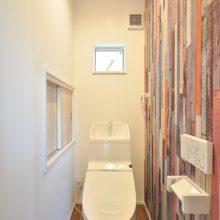 1Fトイレはカラフルな古材風クロスでカジュアルな明るい空間に。あると便利なちょっとした収納はお気に入り。