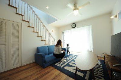 リビング階段や収納扉、そして天井のファンや統一感のある家具のコーディネートで憧れていたカリフォルニアテイストを演出。階段上部の吹抜けとウッドデッキへと繋がる掃き出し窓からは優しい光を採り込む設計となっている。