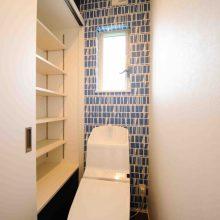 北欧風クロスをチョイスした1Fトイレに設けた大きな収納棚には本を置く予定だとか。