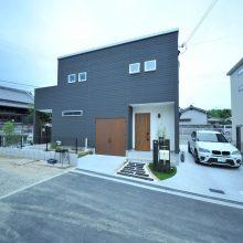 枕木の門柱とアプローチ、そして建物とバランスが良く、ゆったりとした敷地をフルに活用している。