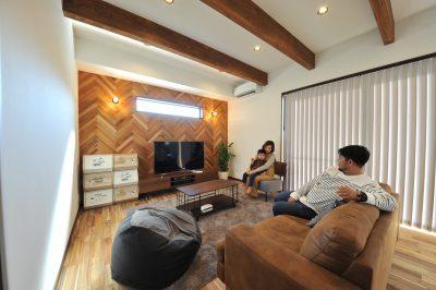 TVボードの壁面には、床材と同じアカシアを採用。ヘリンボーン柄でアクセント。天井の見せ梁もあって素材感のあるくつろぎ空間。