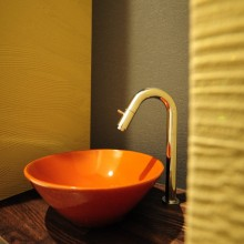 トイレの手洗いスペースも、塗り壁と赤いボウルで和モダンに。ゲストにも大好評。