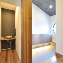 丸窓からの採光で明るい玄関ホール。玄関横の手洗いコーナーはゲストにも使いやすい。