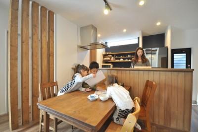 板張りのキッチンカウンターが暖かい雰囲気のダイニング。背面のスリットからこぼれる陽光が柔らかく差し込む。