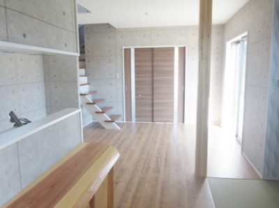 コンクリート打ちっぱなし柄のクロスに、木目のフローリングを合わせました。カウンターはひのき材。タタミコーナーも3帖スペースあります。キッチンは抹茶色の別注色です。