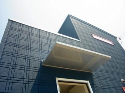 外観の色は、鮮やかな紺色。デザインサッシの赤色と合わせました。玄関のひさしも別注仕様。パワーボードはチェック柄で個性的な家になりました。
