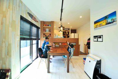 キッチンの腰壁は高めに設計し、木材チップの合板には飾り棚のニッチを設け温もりある食卓に。