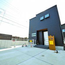 ブラックの外観に木材の門柱とアルミのドアがアクセントに。駐車場はフェンスで囲まれ、子どもたちも安心して遊べるスペース。