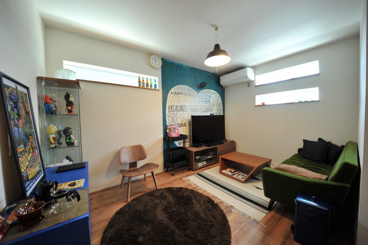 ご主人の大好きなフィギュアや雑貨に囲まれたリビングは遊び心にあふれるアクセントクロスとこだわりの家具でコーディネート。