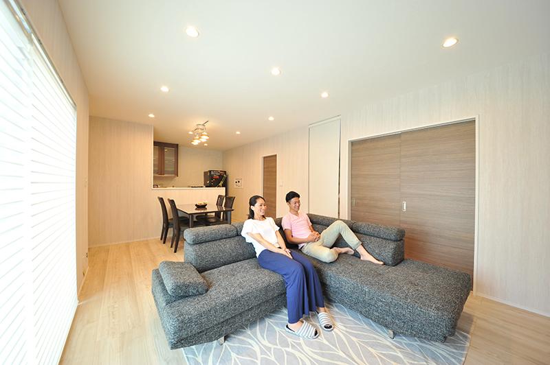 スタイリッシュな家具とナチュラルな内装でまとめられた落ち着いたリビング。ライン状に並んだ照明がラグジュアリーな雰囲気を高め、大きなソファーを置いても開放感を感じさせてくれます。