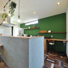 バックセットの壁面はアクセントにグリーンのクロス。キッチン腰壁は外壁と同じ塗り仕上げとタイル貼り。床は職人さんに1枚ずつ色を塗ってもらうなどトコトンこだわりました。